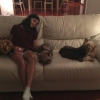 Girl sitting on couch with her dogs